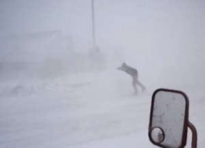 Man tries to withstand the wind in cold winter blizzard